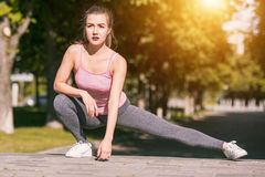 La donna adatta di forma fisica che fa l'allungamento si esercita all'aperto al parco Immagini Stock Libere da Diritti