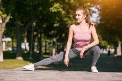 La donna adatta di forma fisica che fa l'allungamento si esercita all'aperto al parco Immagini Stock