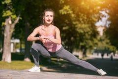 La donna adatta di forma fisica che fa l'allungamento si esercita all'aperto al parco Fotografie Stock