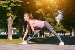 La donna adatta di forma fisica che fa l'allungamento si esercita all'aperto al parco Fotografie Stock Libere da Diritti