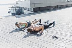 La donna adatta e l'uomo di forma fisica che fanno la forma fisica si esercita all'aperto alla città Fotografia Stock