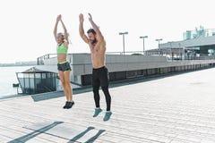 La donna adatta e l'uomo di forma fisica che fanno la forma fisica si esercita all'aperto alla città Fotografie Stock