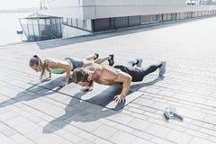 La donna adatta e l'uomo di forma fisica che fanno la forma fisica si esercita all'aperto alla città Fotografia Stock Libera da Diritti