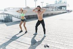 La donna adatta e l'uomo di forma fisica che fanno la forma fisica si esercita all'aperto alla città Immagine Stock