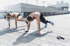 La donna adatta e l'uomo di forma fisica che fanno la forma fisica si esercita all'aperto alla città Fotografie Stock Libere da Diritti