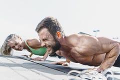 La donna adatta e l'uomo di forma fisica che fanno la forma fisica si esercita all'aperto alla città Immagine Stock Libera da Diritti