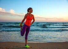 La donna adatta negli sport innesta sulla spiaggia all'allungamento del tramonto Immagini Stock Libere da Diritti