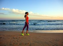 La donna adatta nello sport copre sulla spiaggia alla camminata del tramonto Immagine Stock