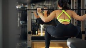 La donna adatta occupa con la parte posteriore del bilanciere davanti allo specchio dentro la palestra stock footage