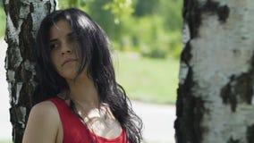La donna adorabile sola sembra tristemente diritta nel parco sotto l'albero, relazione rotta video d archivio