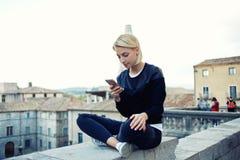 La donna adorabile sta chiacchierando sul telefono delle cellule con gli amici durante il tempo libero è fine settimana Fotografia Stock Libera da Diritti