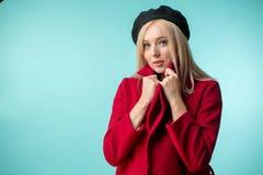 La donna adorabile sta tenendo il collare del suo nuovo cappotto rosso costoso fotografie stock
