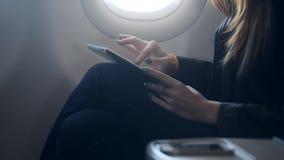 La donna adulta è sedentesi ed usando la tecnologia del computer portatile online mentre aspetta prendendo la grande navata later video d archivio