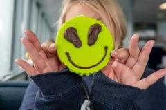 La donna adulta bionda sostiene un biscotto di zucchero di tema straniero per coprire il suo fronte Concetto per divertente, nasc immagine stock