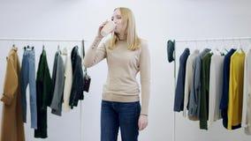 La donna adulta ottiene una tazza del cocktail freddo fresco da qualcuno e la beve che aiuta il suo calore di sconfitta stock footage