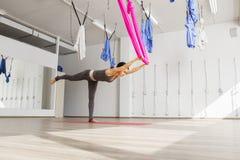 La donna adulta pratica equilibrare la posizione antigravità di yoga del bastone in studio Fotografia Stock