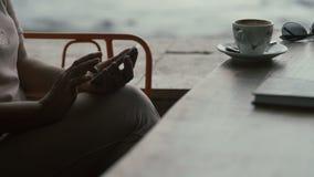 La donna adulta utilizza lo smartphone in caffè archivi video