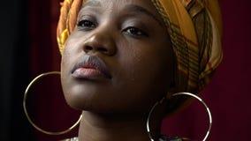 La donna africana con gli orecchini dell'oro in vestiti brillantemente nazionali guarda da parte video d archivio