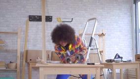 La donna africana con un'acconciatura di afro lavora a legno nell'officina stock footage