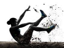 La donna africana di salto in lungo di atletica dell'atleta ha isolato il backgro bianco Immagine Stock