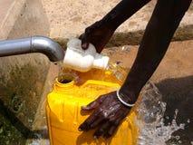La donna africana raccoglie l'acqua fotografie stock libere da diritti