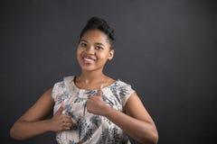 La donna afroamericana con i pollici aumenta il segnale manuale sul fondo della lavagna Immagine Stock