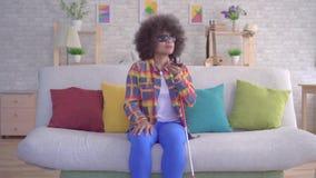 La donna afroamericana con un cieco dell'acconciatura di afro usa l'assistente di voce sul vostro smartphone video d archivio