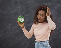 La donna afroamericana turbata esamina la sveglia immagini stock
