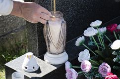La donna al cimitero sta accendendo una candela con una partita sulla tomba immagine stock