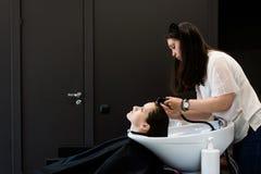 La donna al parrucchiere gli che ottiene i capelli ha lavato e risciacquato ritenere visibilmente buona fotografia stock