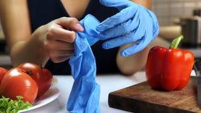 La donna al tavolo da cucina mette sopra i guanti sterili per il taglio delle verdure video d archivio