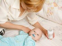 La donna alimenta il bambino immagini stock