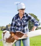 La donna alimenta il vecchio vitello di due settimane dalla bottiglia con il manichino a prato inglese fotografia stock libera da diritti