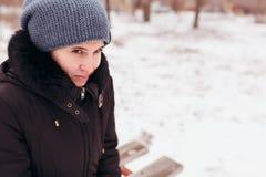 La donna all'aperto pensa nell'inverno dei problemi, si siede su un banco che inclina la testa giù fotografia stock libera da diritti