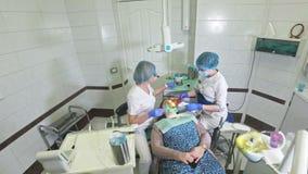 La donna alla clinica del dentista convince il trattamento dentario per riempire una cavità in un dente Ripristino dentario e mat video d archivio