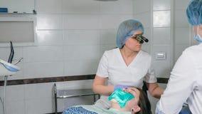 La donna alla clinica del dentista convince il trattamento dentario per riempire una cavità in un dente Ripristino dentario e mat Fotografie Stock Libere da Diritti