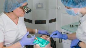 La donna alla clinica del dentista convince il trattamento dentario per riempire una cavità in un dente Ripristino dentario e mat Fotografia Stock