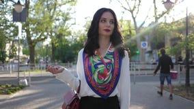La donna alla moda con trucco e l'acconciatura camminano giù la città della via nella stagione calda archivi video