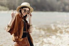 La donna alla moda di boho dei pantaloni a vita bassa che sorride mostrando la pace firma dentro i sunglas immagini stock