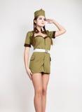 La donna alla moda sexy in uniforme militare e bustina militare, ha messo una mano alla sua testa, saluti fotografie stock