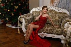 La donna alla moda sta sedendosi vicino al Christmass Immagine Stock Libera da Diritti