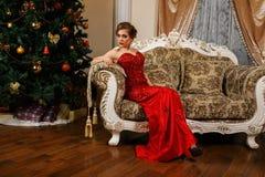 La donna alla moda sta sedendosi vicino al Christmass Fotografia Stock Libera da Diritti