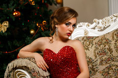 La donna alla moda sta sedendosi vicino al Christmass Fotografie Stock Libere da Diritti