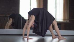 La donna alla moda in vestito nero fa il ponte di asana di yoga vicino allo specchio al rallentatore video d archivio