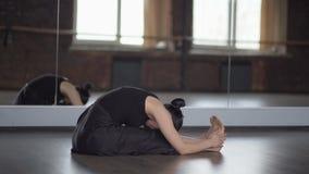 La donna alla moda in vestito nero fa la sbobba nell'yoga - movimento lento video d archivio
