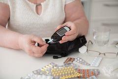 La donna alla tavola La nonna misura il livello di glucosio nel sangue fotografie stock