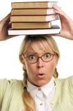 La donna allarmata trasporta la pila di libri sulla testa Fotografia Stock