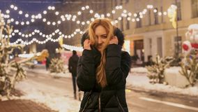La donna allegra balla all'aperto nell'ambito della caduta della neve Signora felice mette il cappuccio con pelliccia sui suoi ha stock footage