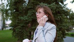 La donna allegra di affari in vetri in vestito leggero va lavorare, la ragazza beve il caffè in parco e parla su uno smartphone archivi video
