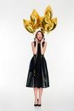 La donna allegra emozionante con i palloni dorati luminosi celebra il suo compleanno Fotografia Stock